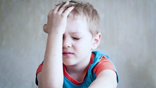 Маленький мальчик держится за голову