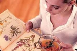 Женщина рассматривает книгу с лечебными травами