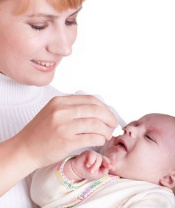 Мама закапывает капли в нос младенцу