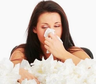 Женщина сморкается в бумажный платок