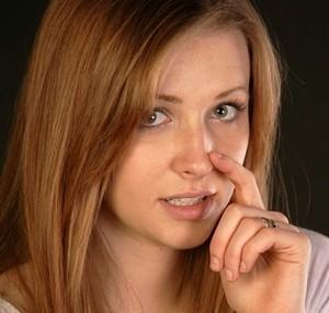 Женщина касается носа
