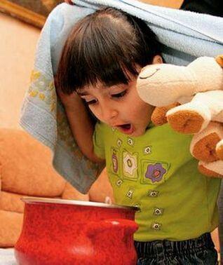 Ребенок накрывается одеялом и наклоняется над кастрюлей