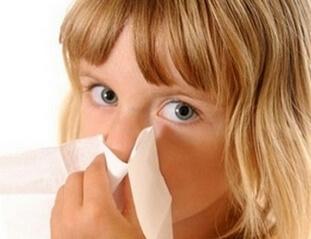 Девочка прижимает платок к носу