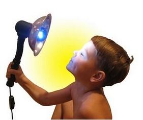 Мальчик греет нос синей лампой