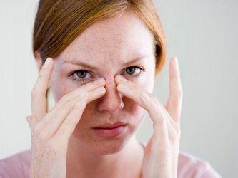 Женщина держится за свой нос