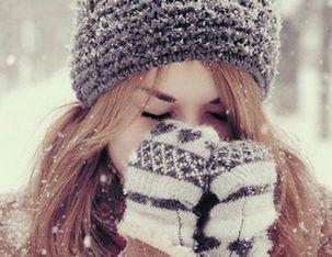 Девушка на улице зимой прижимает руки к носу