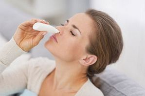 Женщина закапывает капли в нос