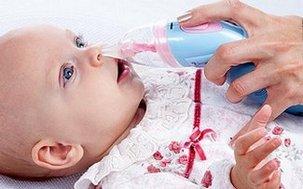 Малышу очищают нос аспиратором