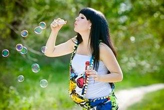 Беременная женщина на прогулке пускает мыльные пузыри