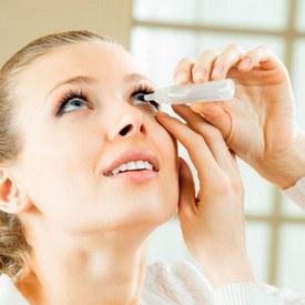 Женщина пользуется глазными каплями