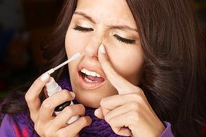 Женщина использует сосудосуживающий назальный спрей