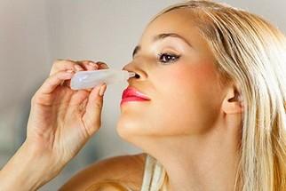 Женщина закапывает в нос капли от насморка