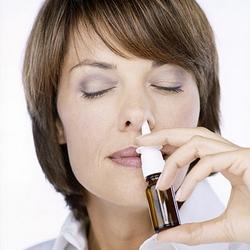 Женщина использует назальный спрей