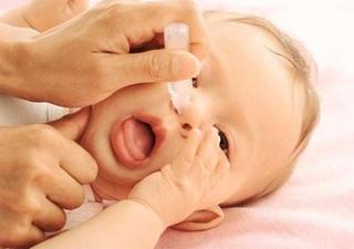 Грудничку закапывают лекарство в нос
