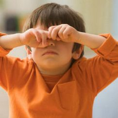 Маленький ребенок закрыл руками глаза