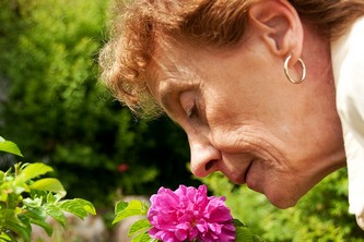Пожилая женщина нюхает цветок