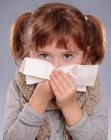 Маленькая девочка сморкается в бумажный платок