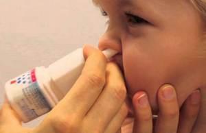 Мама орошает дочке носовой канал с помощью спрея